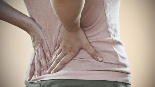 Eine Frau greift sich vor Schmerzen in den Rücken.