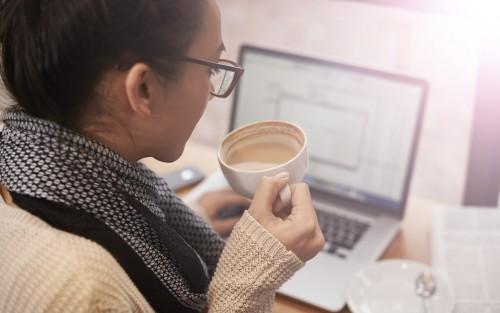 Eine Frau sitzt am Laptop und hält eine Tasse Kaffee in der Hand.