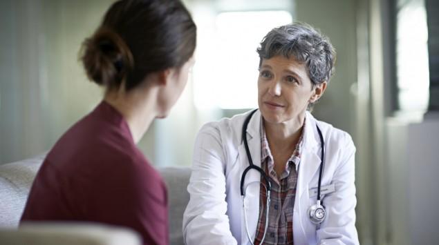 Eine Ärztin legt ihre Hand mitfühlend auf den Unterarm einer ihr zugewandten jungen Frau.