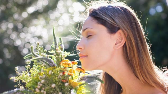 Eine junge Frau riecht an einem Strauß Blumen.