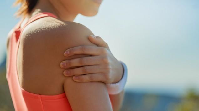 Eine junge Frau im Sportoutfit hält sich die rechte Schulter.