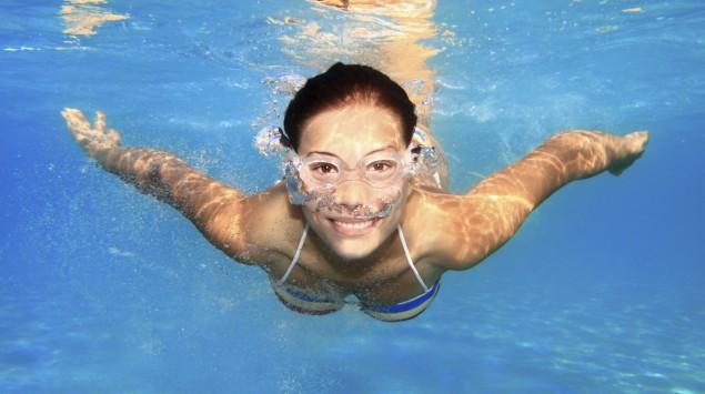 Eine junge Frau mit Schwimmbrille schwimmt unter Wasser.