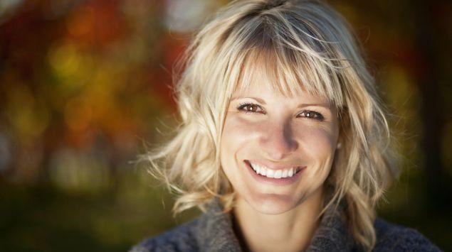Eine Frau mittleren Alters blickt lächelnd in die Kamera.