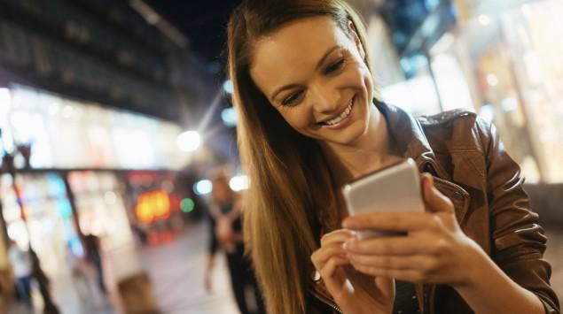 Eine Frau guckt auf ihr Smartphone und lacht.