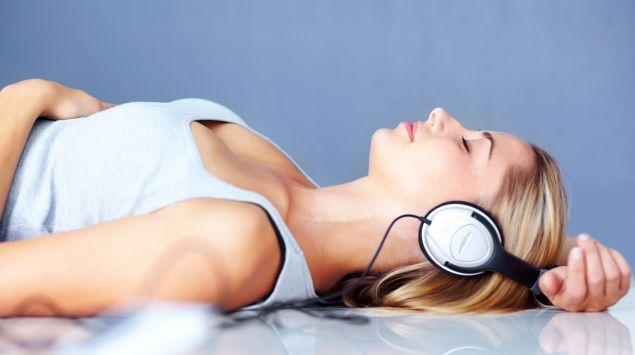 Eine Frau liegt auf dem Rücken und hat mit geschlossenen Augen Kopfhörer auf.
