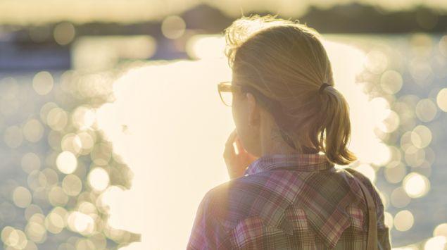 Eine Frau blickt nachdenklich auf einen See.