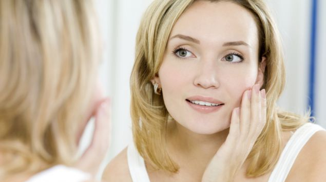Eine Frau betrachtet ihr Gesicht im Spiegel.