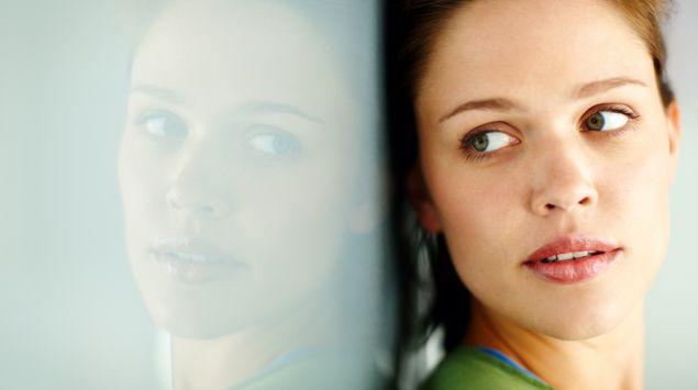 Das Gesicht einer jungen Frau wird von einer Scheibe reflektiert.