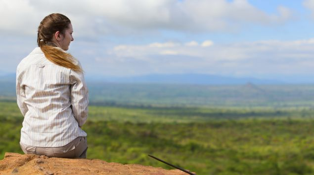 Eine Frau sitzt auf einem Stein und blickt über die Savanne.