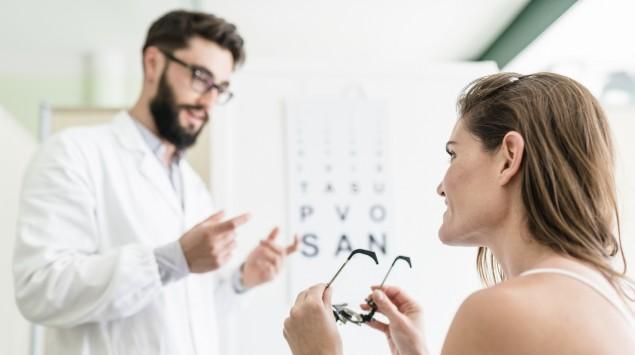 Eine Frau hält eine Brille in den Händen, während sie mit einem Augenarzt spricht.