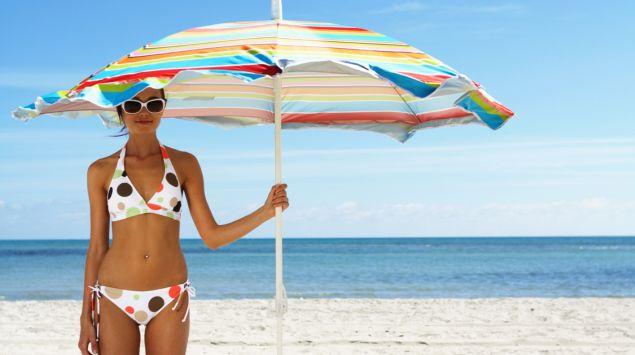 Man sieht eine Frau mit einem großen Sonnenschirm am Strand.^