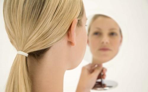 Eine Frau betrachtet sich in einem Spiegel.
