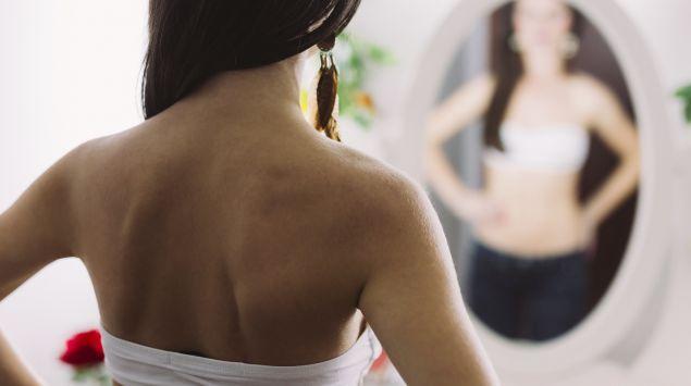 Das Bild zeigt eine junge Frau, die vor einem Spiegel steht.