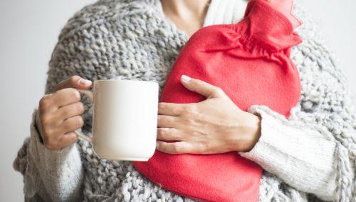 Eine Frau hält eine Tasse in der rechten Hand und eine rote Wärmflaschen im linken Arm.