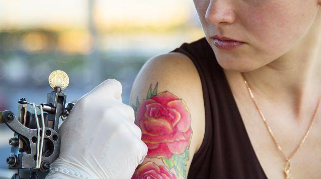 Eine Frau lässt sich am rechten Oberarm tätowieren.
