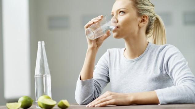 Eine junge blonde Frau mit Pferdeschwanz sitzt an einem Tisch und trinkt aus einem Wasserglas; auf dem Tisch ebefinden sich eine Wasserflasche und ein paar Limettenstücke.