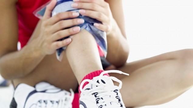 Frau kühlt im Sitzen ihren verletzten Unterschenkel