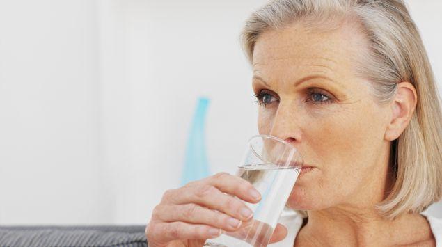 Eine ältere Frau trinkt aus einem Glas Wasser.