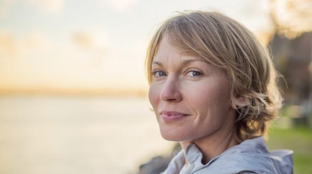 Eine Frau steht am See und blickt den Betrachter zuversichtlich an.