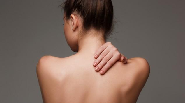 Junge Frau langt sich auf den nackten Rücken