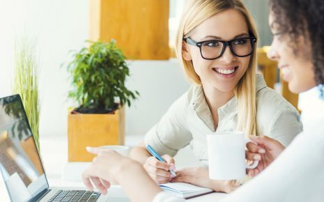 Trockene Augen: Man sieht zwei Frauen im Gespräch vor einem Laptop.