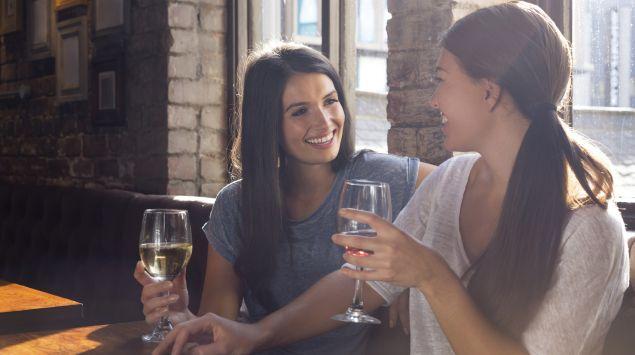 Zwei Frauen trinken zusammen ein Glas Wein.