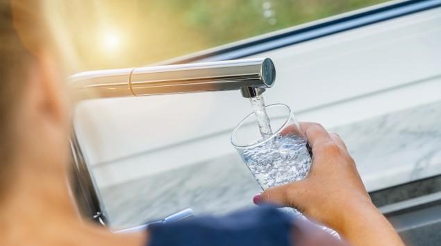 Eine Frau füllt ein Glas mit frischem Leitungswasser.