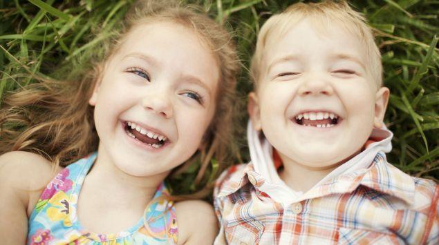 Zwei fröhliche Kinder liegen lachend im Gras.