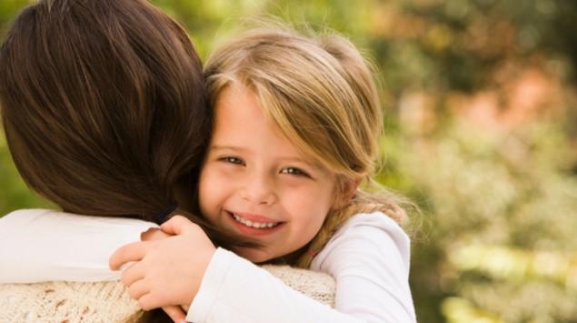 Lachendes Mädchen umarmt eine Frau.