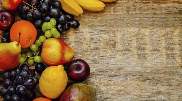 Das Bild zeigt Birnen, Trauben und Bananen auf einem Holzbrett.