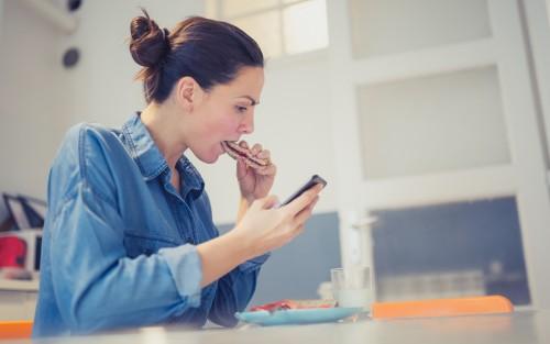 Eine Frau sitzt an einem Tisch und guckt auf ihr Smartphone, während sie ein Brot isst.