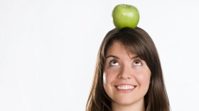 Das Bild zeigt eine Frau mit einem Apfel auf dem Kopf.