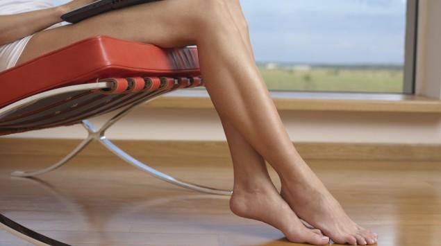 Eine Frau sitzt in einem Sessel und hat einen Laptop auf den Beinen.