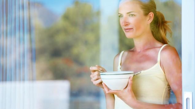 Eine Frau hält eine Schale in der Hand und blickt nachdenklich aus dem Fenster.