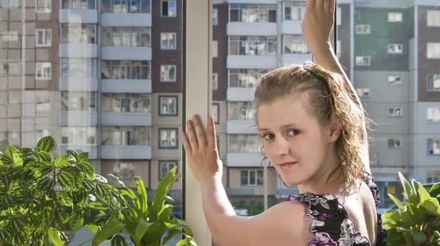 Eine Frau schließt ein Fenster.