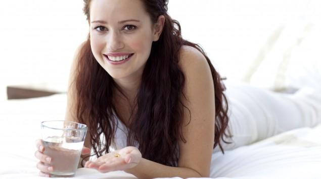 Eine Frau liegt bäuchlings auf dem Bett und hält ein Glas Wasser und eine Tablette in den Händen.