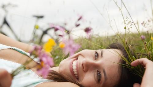 Eine Frau liegt auf einer Sommerwiese. Im Hintergrund sieht man ein Fahrrad.