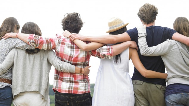 Man sieht eine Gruppe von Freunden Arm in Arm von hinten.