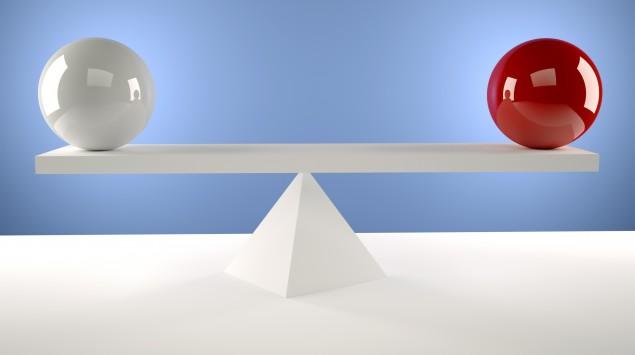Zwei Kugeln balancieren auf einem Balken im Gleichgewicht.