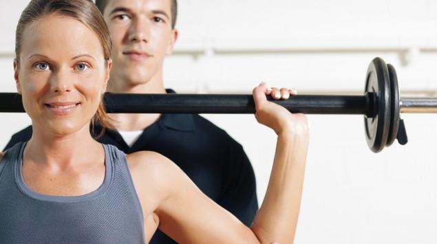 Das Bild zeigt eine Frau und einen Mann mit einer langen Hantel.