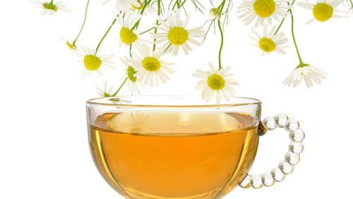 Eine Tasse Tee, daneben einige Kamillenblüten.