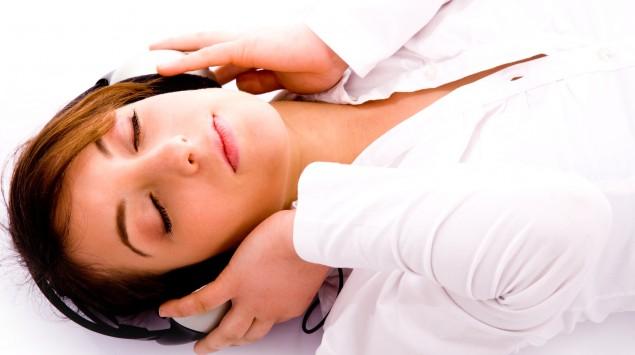 Eine Frau liegt auf dem Rücken und hört Musik über einen Kopfhörer.