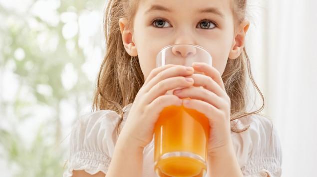 Ein Mädchen trinkt ein Glas Multivitaminsaft