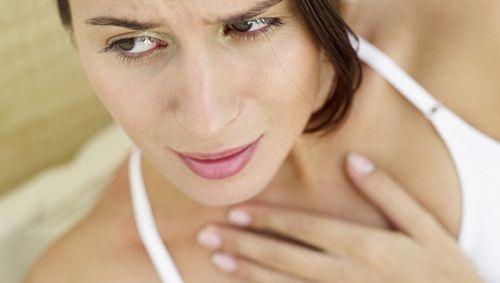 Eine Frau legt sich die Hand an den Hals.