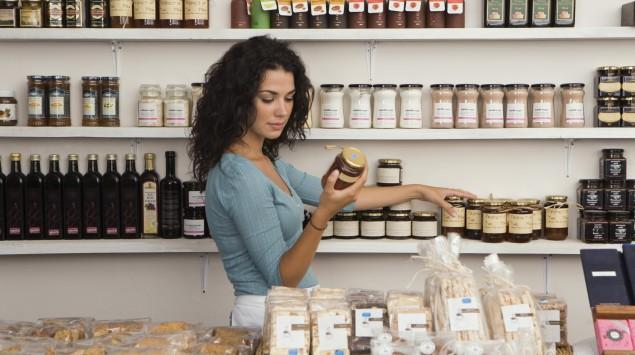 Eine Frau wählt in einem Einkaufsladen Produkte aus.