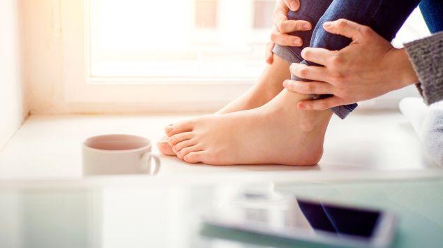 Bei manchen Sitzpositionen kommt es rasch zu eingeschlafenen Füßen. Eine Frau sitzt mit angezogenen Beinen auf einer Fensterbank.