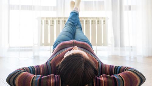 Eine Frau liegt mit unter dem Kopf verschränkten Händen auf dem Fußboden und hat die Füße auf einem Heizkörper abgelegt.