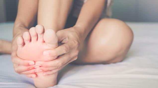 Eine Frau reibt ihren rechten Fuß.
