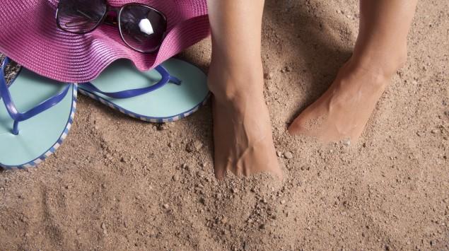 Frau versteckt ihre Füße im Sand.