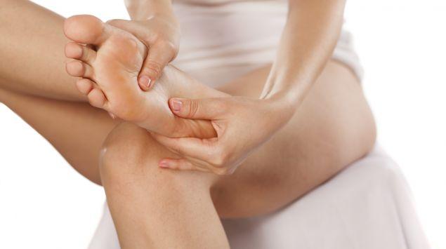 Eine Frau reibt ihren Fuß.